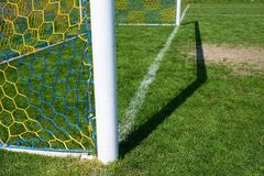 Hang bended soccer nets, soccer football net. Grass on football playground in the background Royalty Free Stock Photo