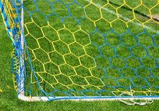 Hang bended soccer nets, soccer football net. Grass on football playground in the background Stock Photography