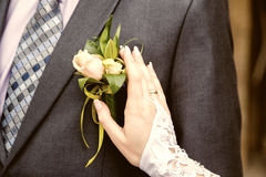 Hang of bride adjusting boutonniere on grooms jacket stock images