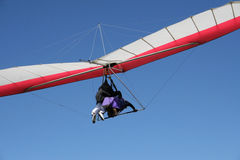 The Hang Glider. 2 people flying tandem on a red hang glider against a blue sky background Royalty Free Stock Photo