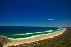 Hang Glider Flying Over Beach Stock Photos