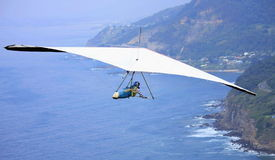 Hang glider flying over the ocean Stock Photography