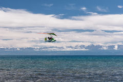 Hang-glider hovering over emerald water. Hang-glider hovering over pure emerald water of the lake near mountains Stock Photo