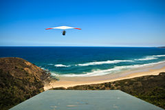 Hang Glider Launches From Hill Above Beach Royalty Free Stock Photos