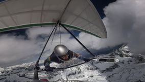 Hang glider pilot fly with his wing on high altitude between clouds above snow mountain peaks royalty free stock photos