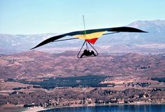 Hang Glider Soars High Above Lake Elsinore, CA, USA. A hang glider soars the peaks of Edwards Canyon high above Lake Elsinore, California, USA; This foot royalty free stock images
