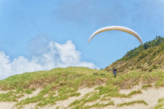 Hang glider soars low over grassy dunes Stock Image