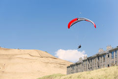 Hang Glider soars over beach lodging at Pacific City Royalty Free Stock Photo