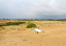Hang glider student landing on sand dunes in North Carolina. Student prepares for landing with an instructor from the Kitty Hawk Kites Hang Gliding School on the stock images