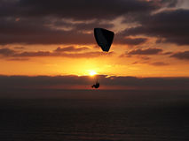 Hang glider in sunset, far. Hang glider over ocean sunset Royalty Free Stock Images