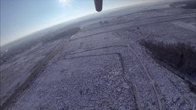 A hang glider takes off over a snowy winter meadow and forest. stock video footage