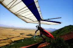 Hang-glider taking off. Over wheatfields, on a mountain slope Stock Photos