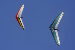 Hang Gliders. Against blue sky stock photo