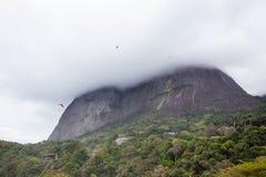 Hang gliders in Pedra da Gavea on a cloudy day Stock Image