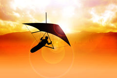 Hang Gliding. Silhouette of a man figure gliding during sunrise Royalty Free Stock Photos