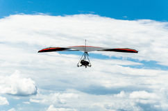 Hang gliding flight in blue sky with clouds Stock Photos