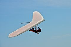Hang gliding man. On a white wing with sky in the background Stock Images