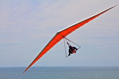 Hang gliding man on an orange wing in the sky. Hang gliding man on an orange wing with sky in the background Royalty Free Stock Photography