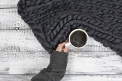 Hang with hot coffee. Woman hand in warm sweater holding cup of hot coffee near super chunky woven blanket. Top view point Stock Photo