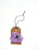 Hang tag with a flower. Hand stained hang tag with a purple flower Royalty Free Stock Photography