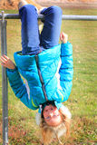 Hang on. A young preteen girl hanging fearlessly from a bar upside down smiling wearing a warm coat Royalty Free Stock Image