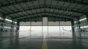 Hangar for aircraft with large open gate at sunny summer day. Large aircraft hangar open the gates stock video footage