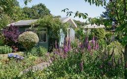 Hangar de jardin entouré par un beau jardin décoratif Images libres de droits