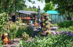 Hangar de jardin et maison verte entourés par un beau décoratif Image stock