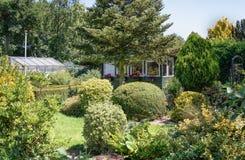 Hangar de jardin et maison verte entourés par un beau décoratif Photo stock