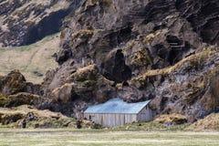 Hangar de la ferme de Drangshlid construite dans la formation de roche Drangurinn en Islande Photo stock