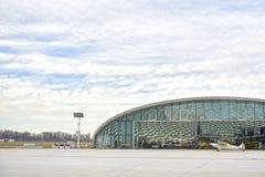 Hangar med flygplanet och blå himmel En liten nivå står nära hangaren och förbereder sig att ta av Hangar från exponeringsglas arkivfoto