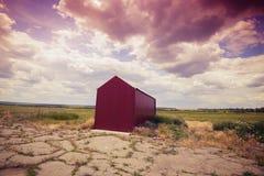 Hangar rojo solitario en el campo de aviación abandonado Foto de archivo libre de regalías