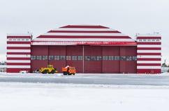 Hangarbyggnad i vinter i en snöig flygplats royaltyfri fotografi