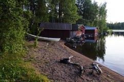 Hangars à bateaux sur le lac au coucher du soleil Photographie stock