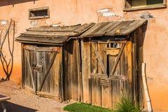 Hangars en bois de stockage de vintage contre le vieil immeuble de brique d'Adobe Images libres de droits