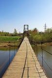 Hangbrug over de rivier dichtbij de hydro-elektrische installatie Stock Foto