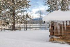 冰周期hange一个原木小屋冬天的屋顶 免版税库存图片