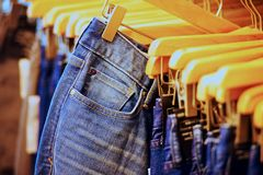 Hanged blue jeans. Row of hanged blue jeans in a shop Stock Images