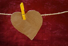 Hanged Heart. Heart-shaped cardboard pieces hanged in a rope with pins Stock Photo