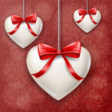 Hanged hearts with red bow for Valentine`s Day. Hanged white hearts with red gift bows, on red floral pattern background. Vector illustration for Valentine`s Day Royalty Free Stock Photography