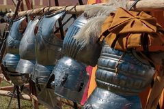 Hanged Metallic Armors in Line in front of Red and Yellow Tent Stock Photo