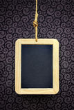 Hanged Slate. Writing slate hanged with a rope over a wallpaper with curly pattern Royalty Free Stock Images