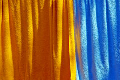 Hanged towels. Background of orange and blue towels hanged to dry Stock Image
