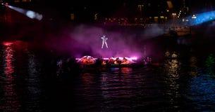 Hangende acrobaat met de prestaties hieronder in purper licht stock fotografie