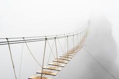Hangende brug in mist stock afbeelding