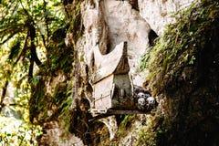 Hangende doodskisten, graven Oude doodskist met schedels en beenderen dichtbij op een rots Begrafenissenplaats, begraafplaats Ket Stock Foto