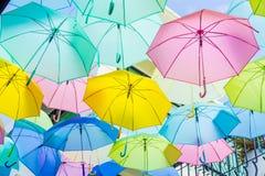 Hangende kleurrijke paraplu's, op de straat en de blauwe hemel Stock Foto