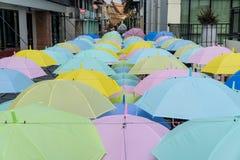 Hangende kleurrijke paraplu's, op de straat en de blauwe hemel Hoogtesleutel Royalty-vrije Stock Afbeeldingen