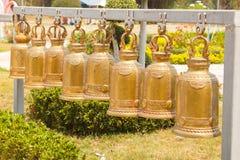 Hangende klok Het grote gouden klok hangen in rijen op een staalstraal Stock Foto's