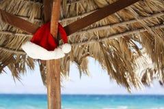 Hangende Santa Claus-hoed op palmy zonnescherm stock foto